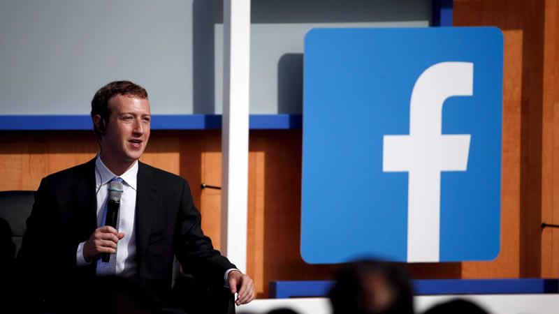 Mark Zuckerberg, fundador do Facebook vestindo terno e gravata, com microfone sem fio na mão e usando fone de ouvido, tendo ao fundo, em um painel, o logotipo do Facebook