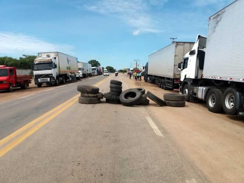 Em uma rodovia caminhões estão estacionados em ambos os acostamentos da mesma tendo uma barreira de pneus em um dos sentidos da rodovia. Também se vê alguns caminhoneiros ao lado da rodovia reunidos em grupo. Trafegando na rodovia se vê um veículo de passeio e duas motocicletas