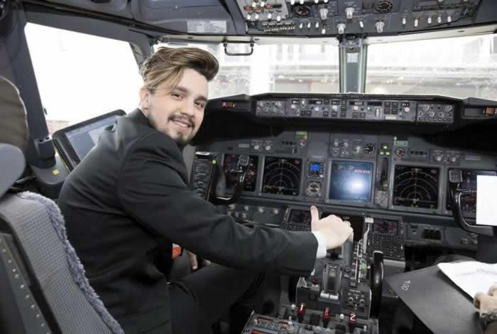 Luan Santana sentado na poltrona do piloto de um avião simulando estar pilotando o avião