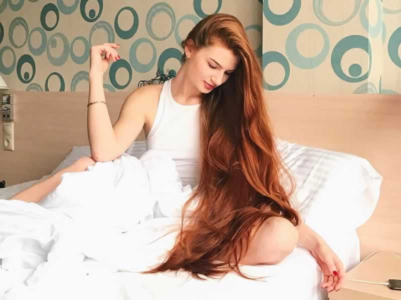 A Anastasiya Sidorova sentada em uma cama olhando seus longos sobre o colo