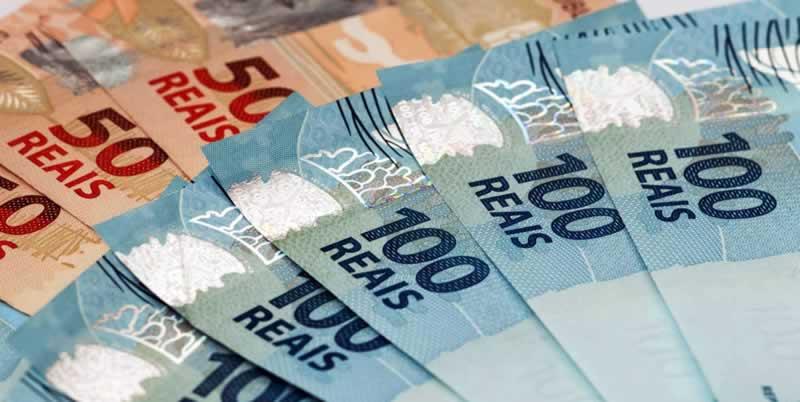 Cédulas de R$ 100,00 sobrepostas sobre cédulas de R$ 50,00