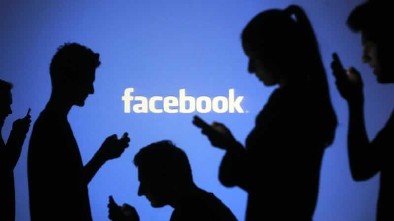 Cinco usuários do Facebook, na penumbra e com um fundo azul,  com seus smartphones nas mãos. A palavra