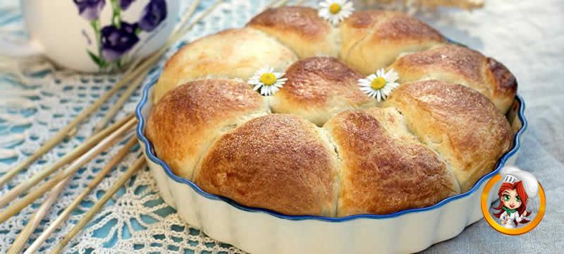 A rosca da vovó enfeitada com 3 margaridas dentro de uma travessa sobre uma mesa decorada com uma toalha de croche e um bule de chá