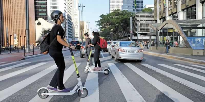 Em uma faixa de pedestres próxima à Estação Consolação do Metrô na Avenida Paulista em São Paulo, além de pedestres atravessando na faixa, também o fazem duas moças utilizando patinetes elétricas. Ambas estão usando capacete e carregam mochilas nas costas