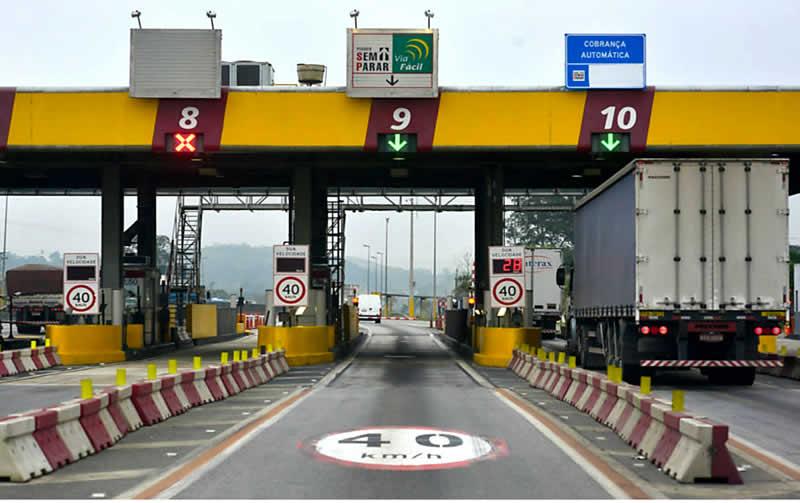 Praça de pedágio mostrando três cabines de pedágio automáticas sinalizadas com o limite de velacidade de 40 km por hora, Na cabine da direita, tem um caminhão baú chegando na mesma e o radar mostra a velocidade deste caminhão que é de 28 km por hora