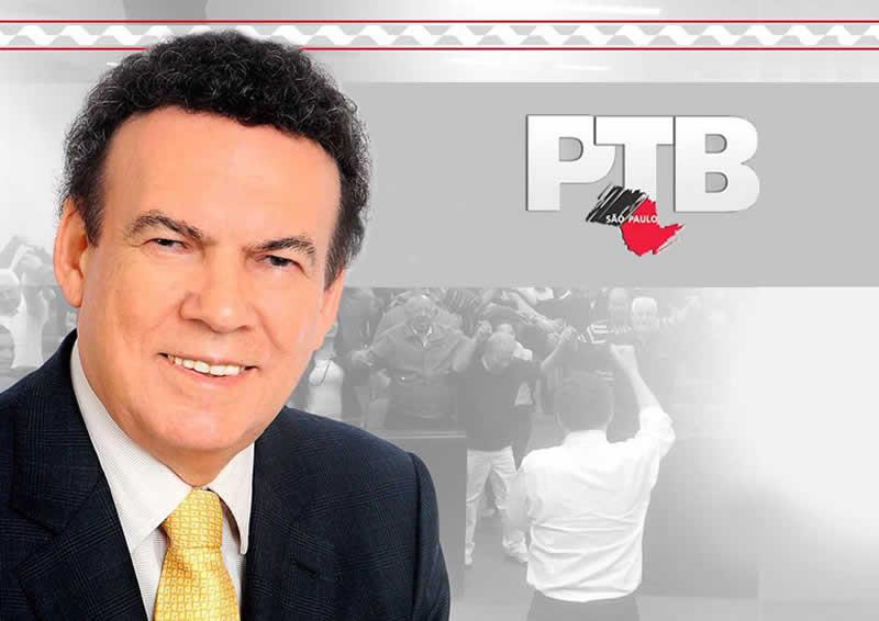 Close o Deputado Campos Machado do lado esquerdo da imagem, sorridente e trajando terno e gravata, e do lado direito a logomarca do PTB/SP, ao fundo das imagens e em marca d'água de nota a imagem de um auditório com um palestrante de costas se dirigindo à platéia