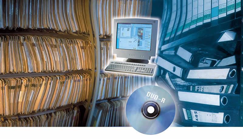 Do lado esquerdo, uma estante com centenas de pastas suspensas arquivadas. Do lado direito, uma estante com pastas pretas para arquivo. Ao centro a imagem de um computador e um DVD-R
