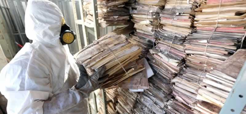 Pessoas usando Equipamento de proteção individual faz a limpeza de parteleiras de arquivos