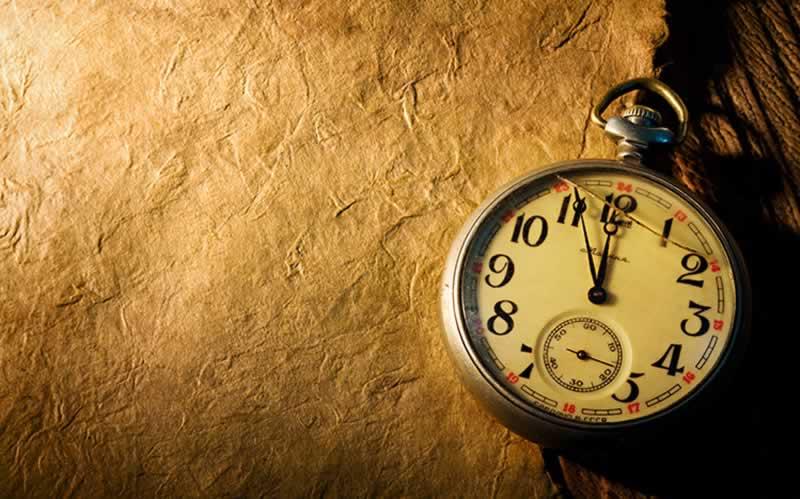 Relógio representando o passar do tempo e papiro sem imagens ou escrita representando o apagar da memória