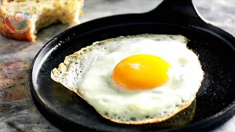 Um ovo frito em uma frigideira de ferro. Ao lado esquerdo superior da frigideira se vê uma fatia de pão de forma já mordida