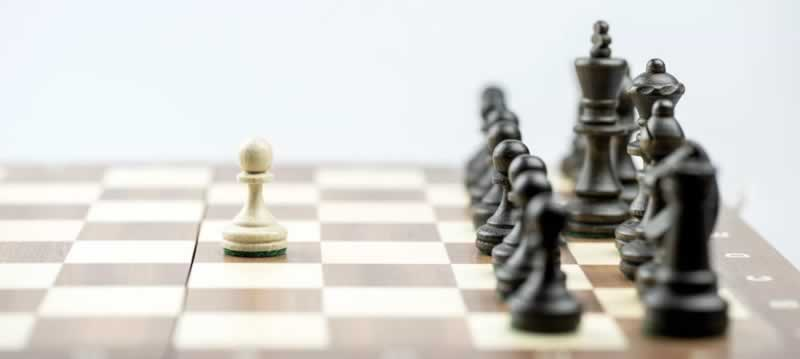 Um tabuleiro de xadrez com as peças pretas todas elas posicionadas em seus respectivos lugares e diante delas, apenas um peão branco