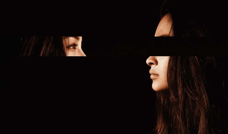 Em um fundo preto, imagem do rosto de uma mulher de perfil com a parte dos olhos recortada, separada e invertida, onde o olhar dela visualiza o próprio rosto