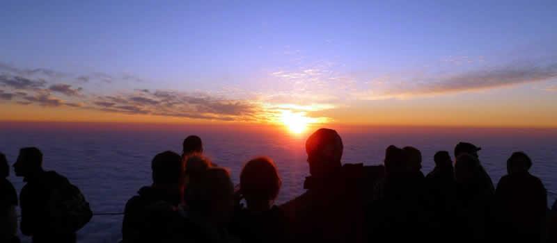 Nascer do sol sobre o mar sendo observado por um grupo de pessoas que estão em um mirante