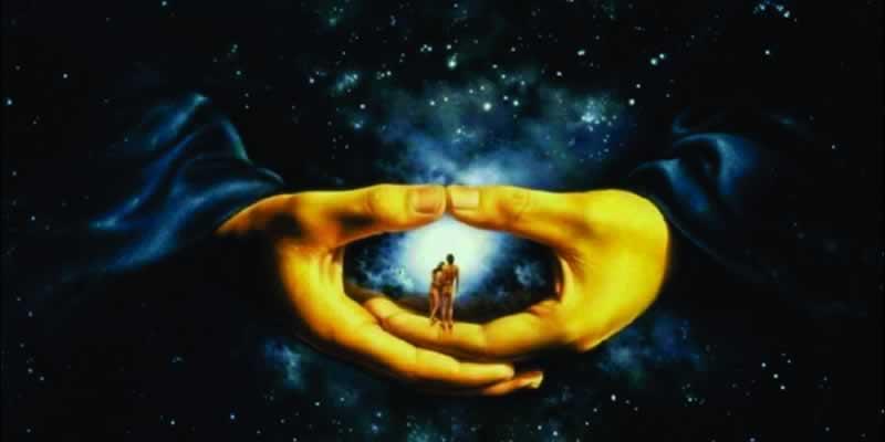 Tendo o espaço sideral ao fundo, um casal está entre duas mãos gigantescas que, unidas, parecem proteger este casal. Estas duas mãos, aqui neste artigo, estão representando o Universo