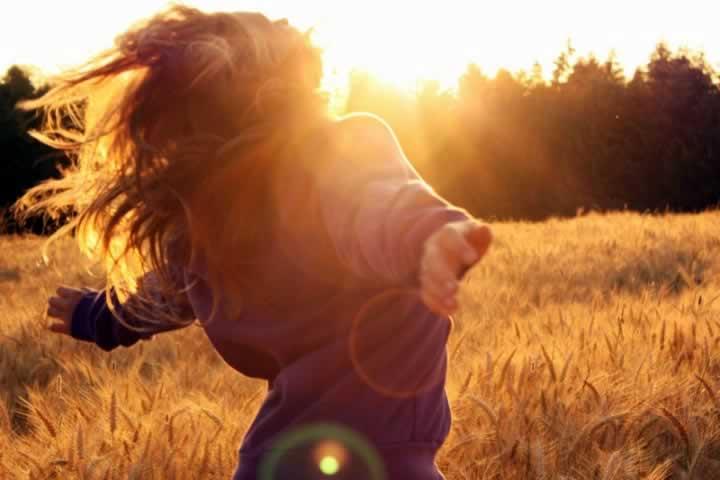 Mulher, ao entardecer, no meio de uma plantação de trigo, de braços abertos, cabeça erguida para o céu e cabelos compridos soltos ao vento