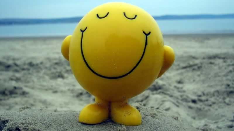 Boneco de um Emoticon sorrindo na praia