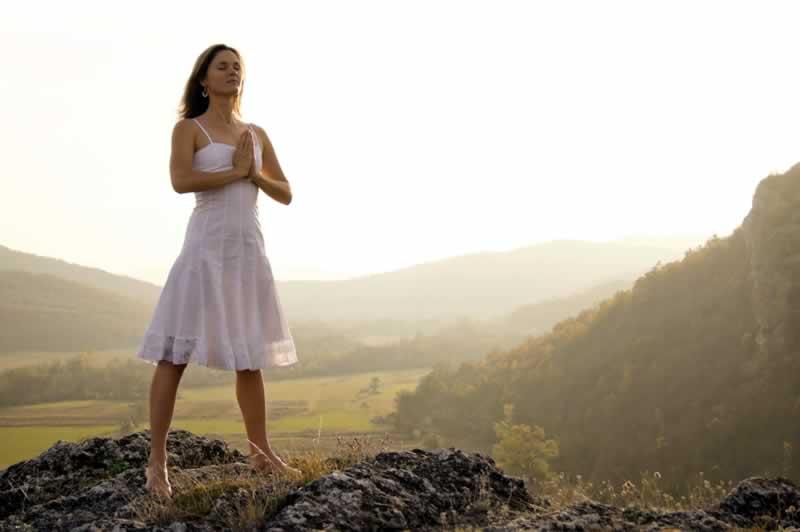 Mulher, de pé, descalça, meditando no topo de uma montanha envolta por uma leve névoa, tendo ao fundo outras montanhas e um vale onde se nota uma lavoura